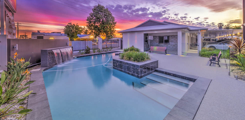 Relax by our Resort style pool with a beautiful cascading waterfall and surrounded by chairs, gardens and a BBQ Area at Western Downs Motor Inn - Miles.